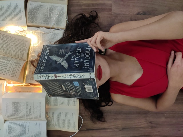 women cover her face by a book